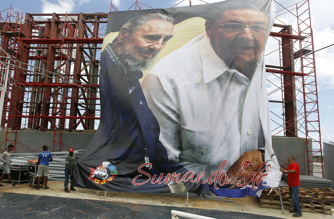 BROTHERS. Workers unfurl a giant banner with an image of Cuban President Raul Castro (R) with his brother and leader of the Cuban revolution Fidel, who turns 90 on August 13, in Havana, Cuba, August 12, 2016. Photo by Ernesto Mastrascusa/EPA