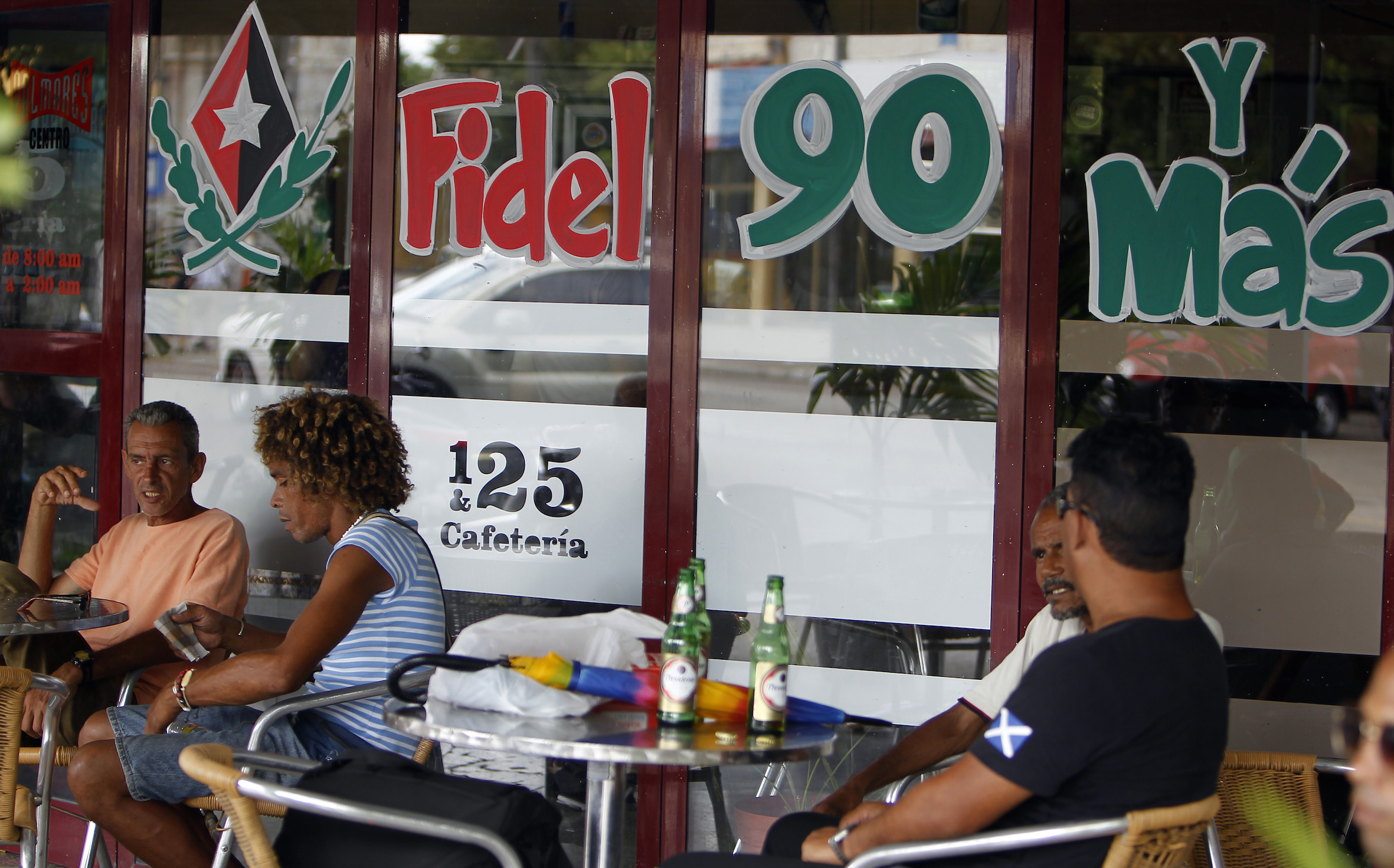 FIDEL TURNS 90. Several people drink beer in Havana, Cuba, August 9, 2016, next to a message marking the 90th birthday of Cuban Revolution leader Fidel Castro this August 13. Photo by Ernesto Mastrascusa/EPA
