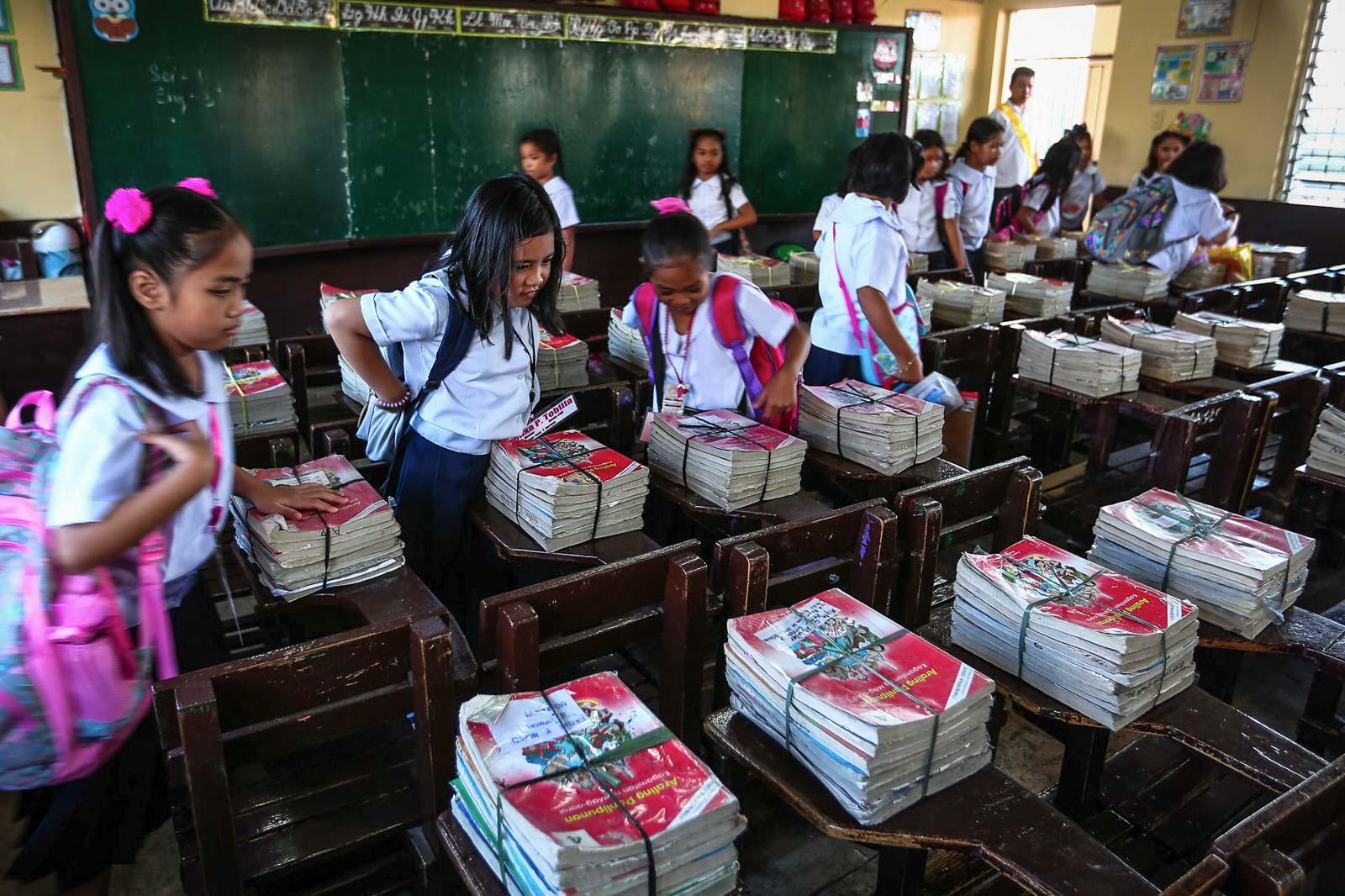 'NEW'. Students of the Corazon Aquino Elementary School in Quezon City receive their books.