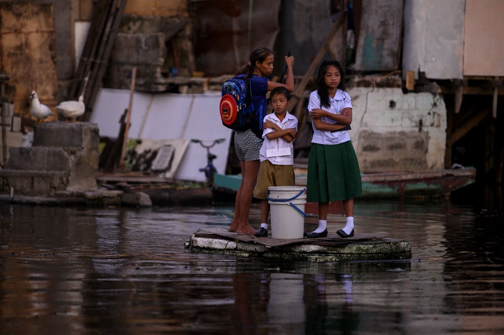 BOAT TO SCHOOL. Panghulo 1 Elementary School students living inside the flooded Artex Compound in Malabon ride on makeshift boats on their way to class. Photo by Noel Celis/AFP