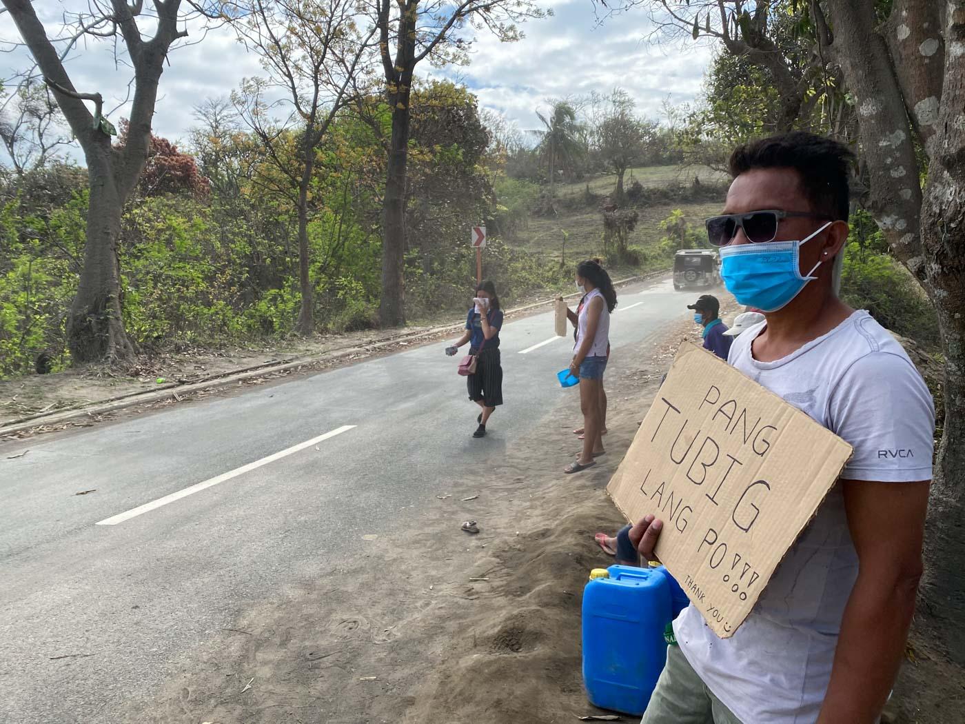 'PANG-TUBIG LANG PO.' Barangay San Guillermo resident Marlon Rosima asks for water from passing vehicles on January 31, 2020. Photo by Mara Cepeda/Rappler