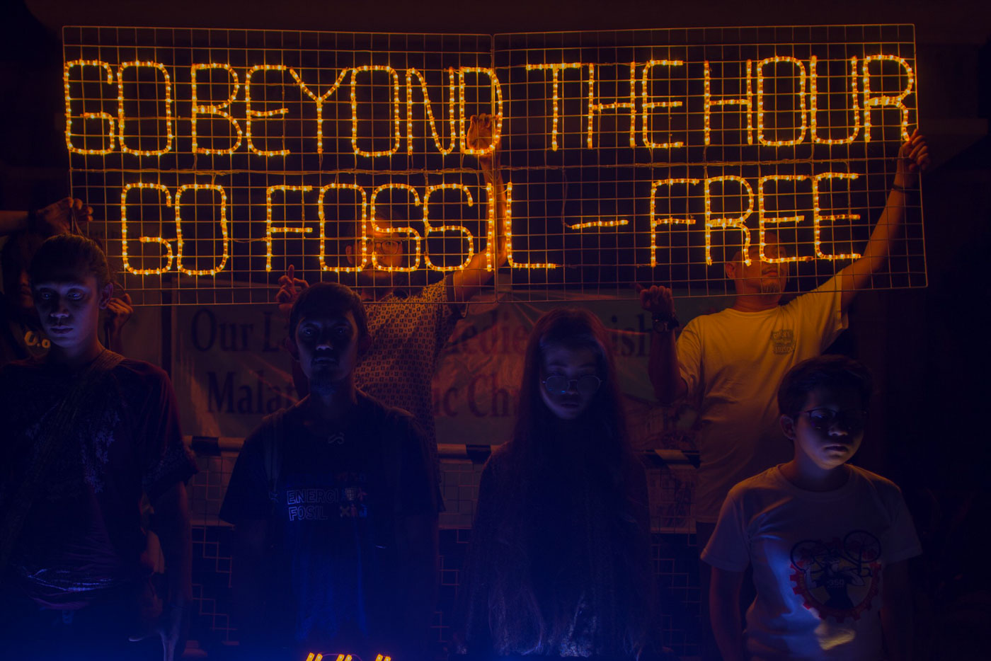 SAVE THE ENVIRONMENT. Climate activists from 350.org Pilipinas, light up LED banners at Malate Catholic Church. Photo by Maria Tan/Rappler