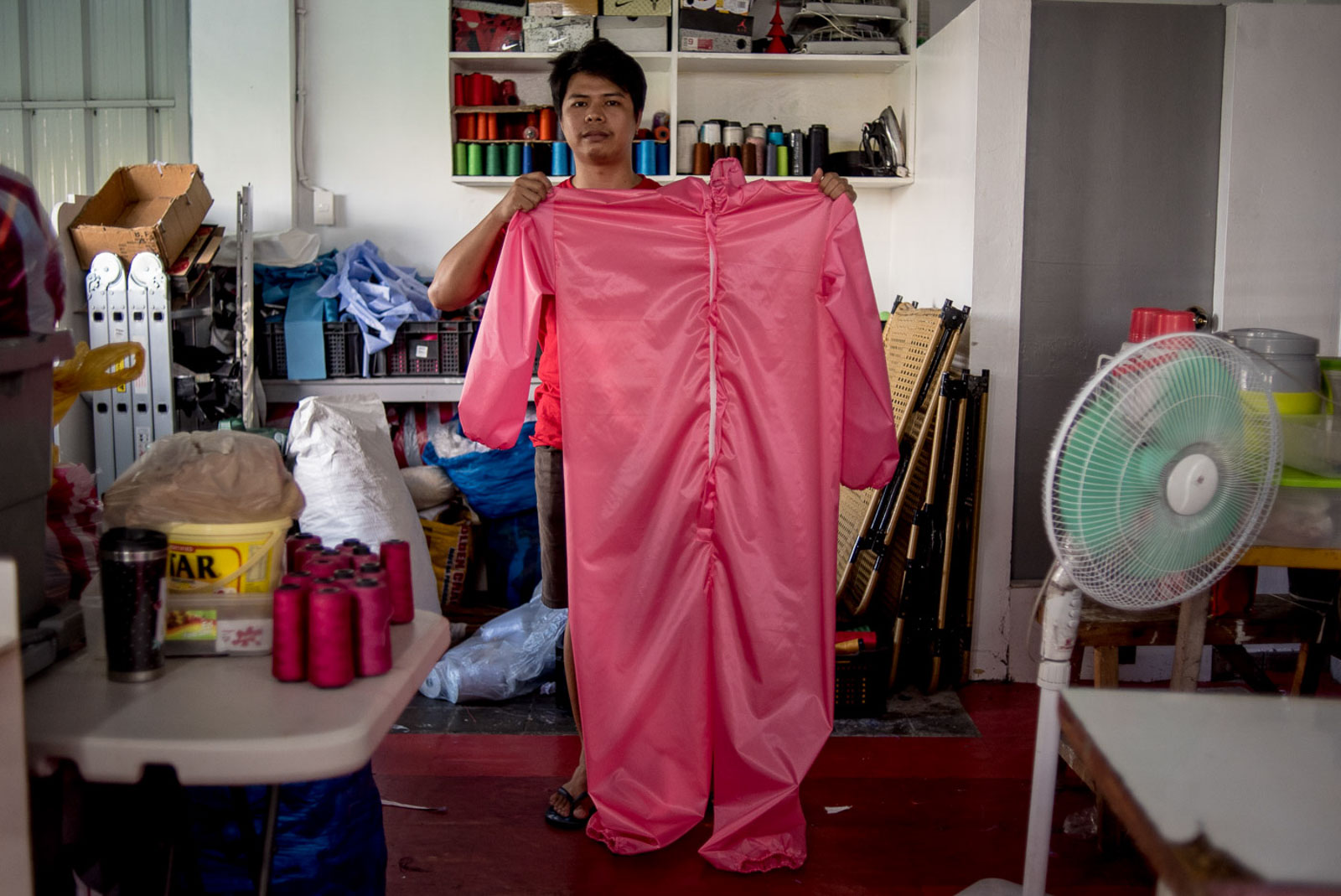 FINAL PRODUCT. A tailor holds a newly sewn PPE suit.