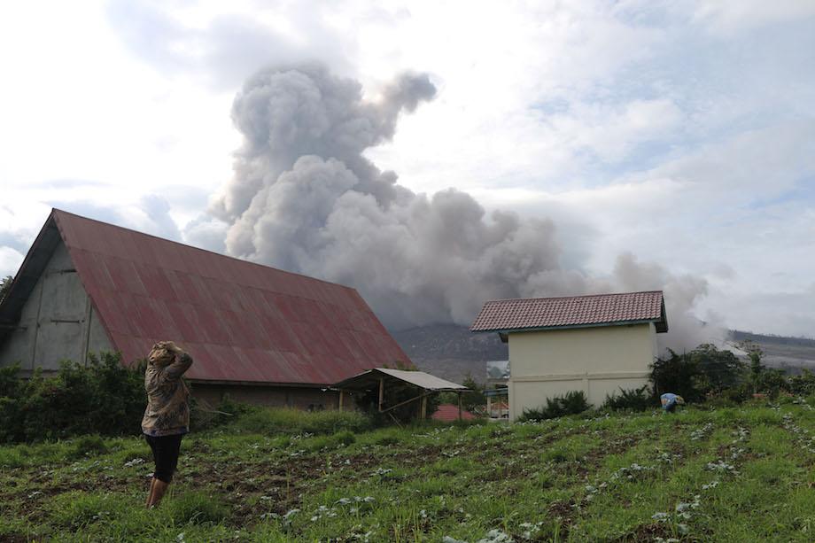RUMAH PETANI. Petani melihat Gunung Sinabung mengeluarkan material vulkanis disertai awan panas ketika erupsi, tampak dari Desa Tiga Serangkai, Karo, Sumatera Utara, Minggu (15/11). Gunung Sinabung masih berstatus Awas (Level IV) sejak 2 Juni 2015 dan sedikitnya 7.000 warga masih mengungsi. ANTARA/Irsan Mulyadi