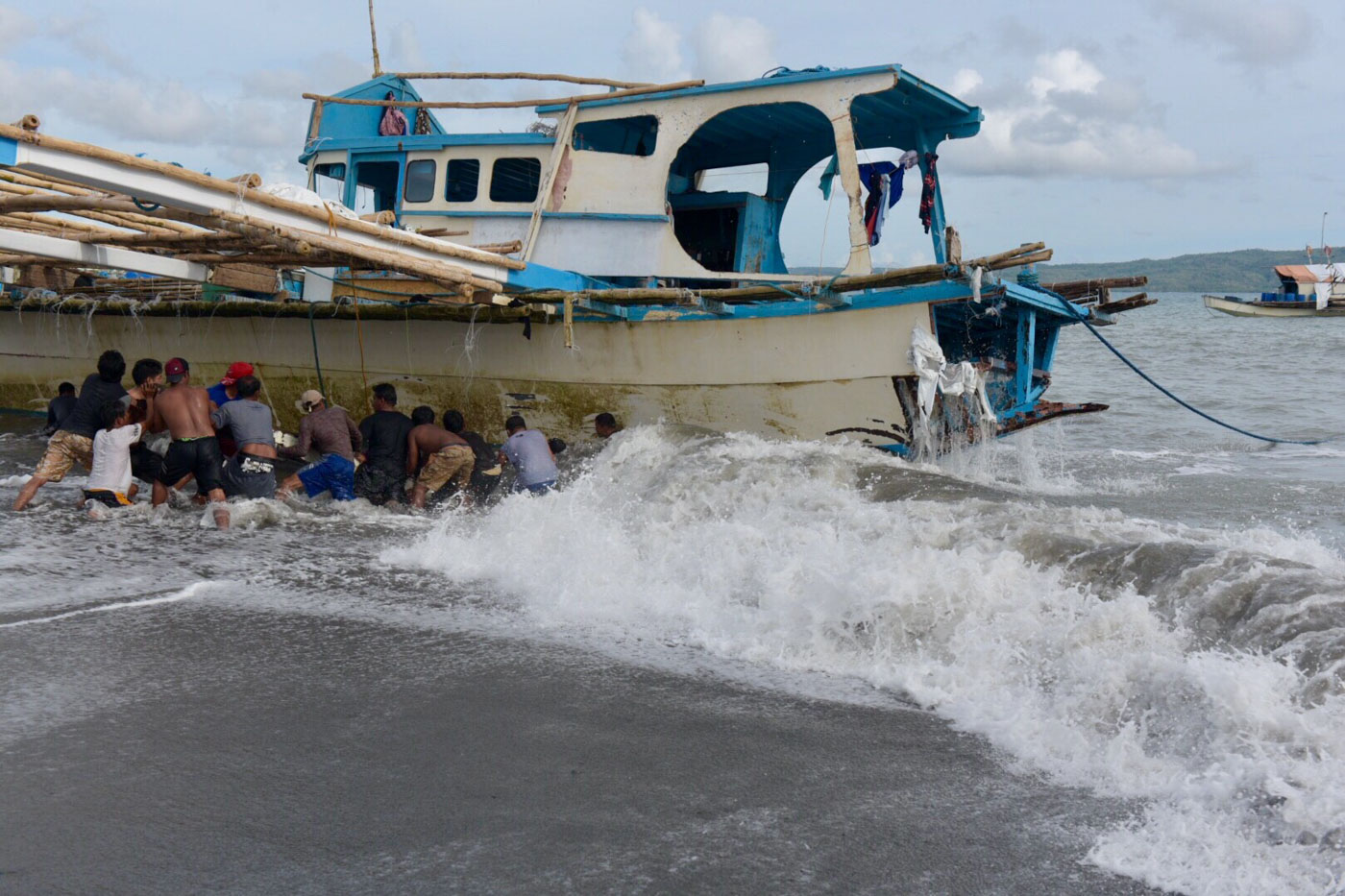 Fishermen pull the F/B Gem-Ver, the Filipino boat sunken by a Chinese vessel near Reed Bank, towards the shore of Barangay San Roque, San Jose, Occidental Mindoro on June 15, 2019.