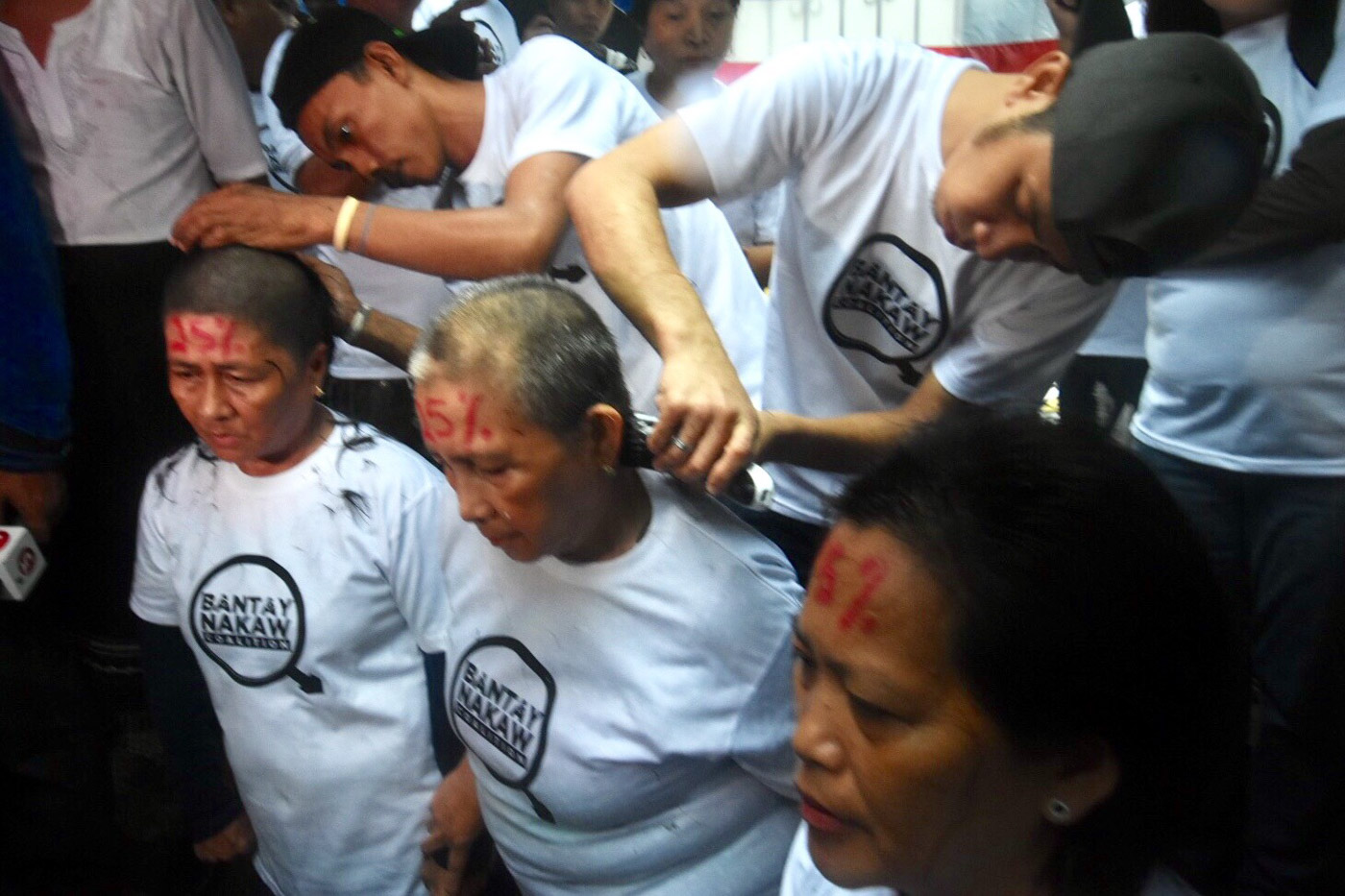 SYMBOLIC HAIRCUT. Members of Bantay Nakaw coalition troop to the Supreme Court amid the rain on June 11, 2018, to shave their heads in protest of the 50% shading threshold applied by the Presidential Electoral Tribunal. Photo by Angie de Silva/Rappler