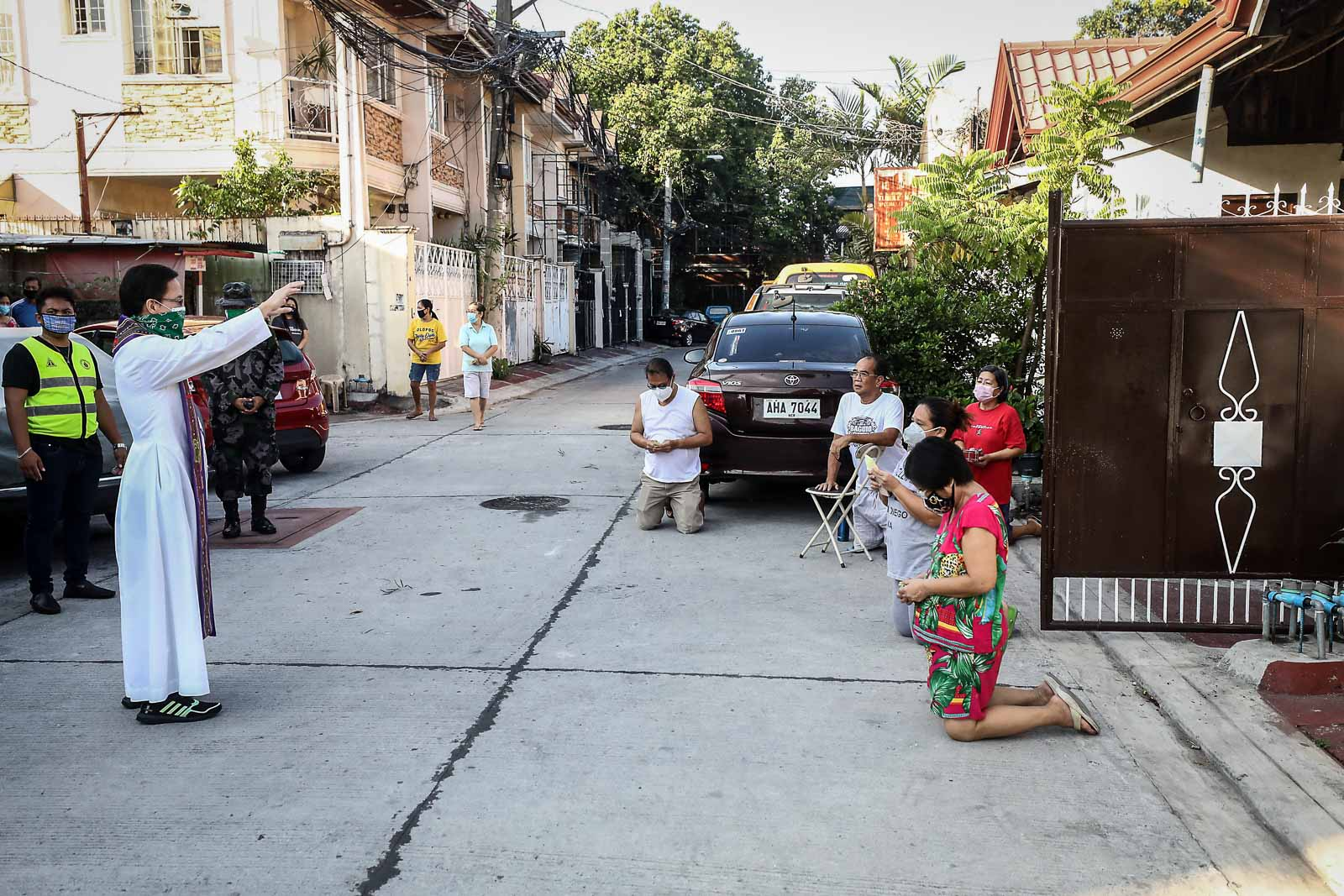 FORGIVENESS. From a safe distance, a priest imparts general absolution, or the forgiveness of sins, to residents of Barangay Villa Maria Clara in Cubao, Quezon City, on Holy Tuesday, April 7, 2020. Photo by Ben Nabong/Rappler
