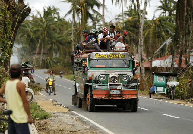 Filipinos ride a jeepney, a popular mode of transport, at a road in the typhoon hit town of San Julian, Samar island, Philippines, 10 December 2014. Typhoon Hagupit slammed into the eastern coast of Samar Island, 560 kilometres south-east of Manila on 06 December, destroying more than 30,000 homes, knocking out power and damaging some key infrastructures. Some roads were impassable due to floods, landslides and toppled trees or electric posts. Photo by Francis R. Malasig/EPA