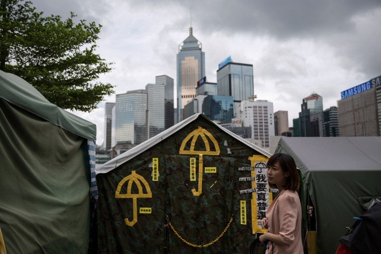 In a picture taken on June 13, 2015, a woman stands in front of yellow umbrellas, a symbol of the pro-democracy movement, stuck on a tent outside the government headquarters in Hong Kong. Dale de la Rey/AFP