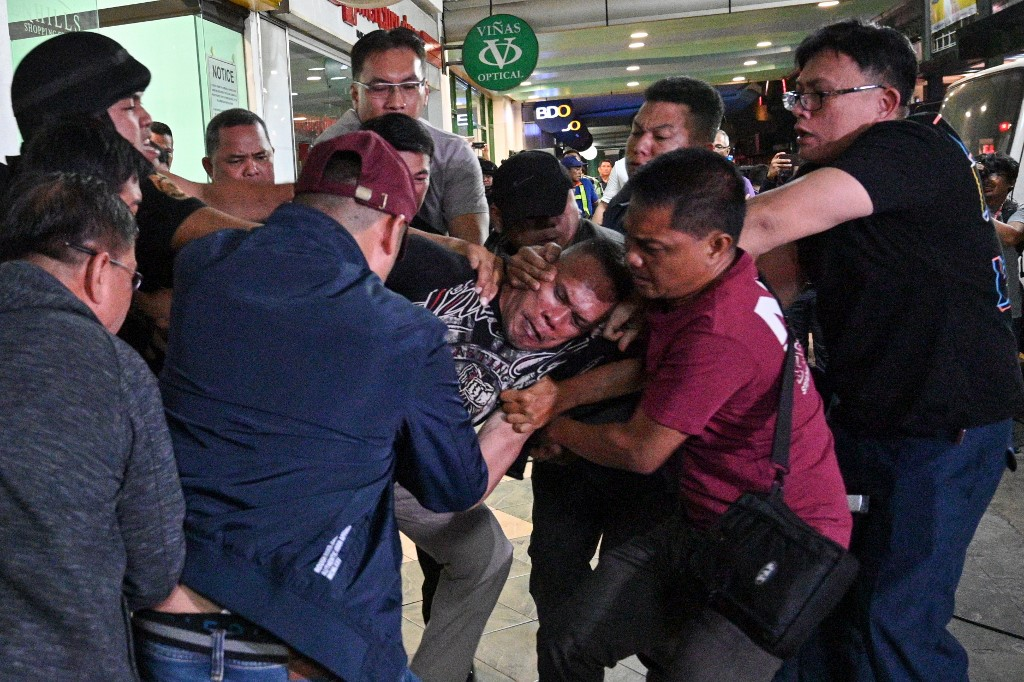 ARRESTED. Policemen subdue hostage taker Alchie Paray (center) after he surrenders outside a mall in Greenhills, San Juan, Metro Manila on March 2, 2020. AFP photo