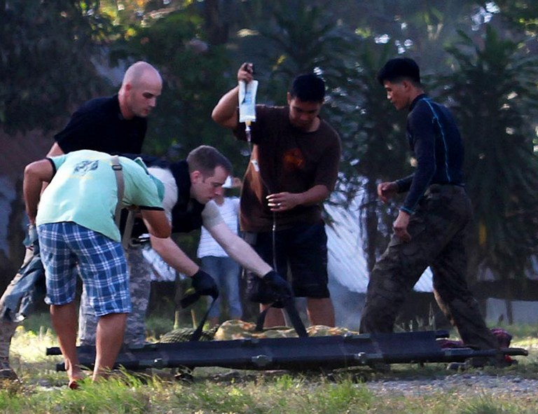 UNFINISHED BUSINESS. In this file photo, US military personnel (L) help their Philippine counterparts prepare to load an injured police commando from one stretcher to another and onto a waiting US military helicopter in the town of Mamasapano on January 26, 2015, following clashes with Muslim rebels. File photo by AFP
