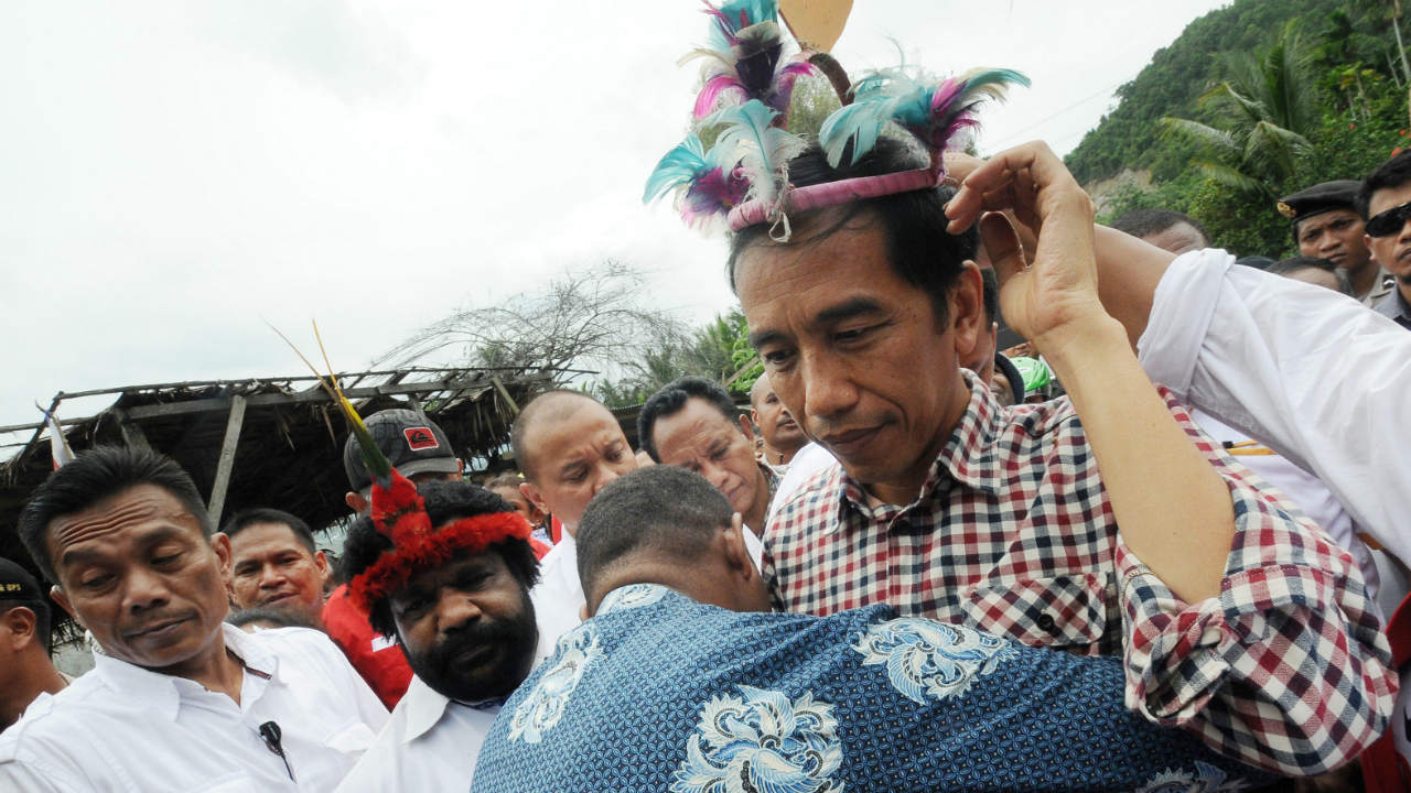 PROMISES. Joko Widodo (R) wears a Papuan traditional head wear during his presidential campaign rally in Jayapura, Papua, in June 2014. Photo by EPA