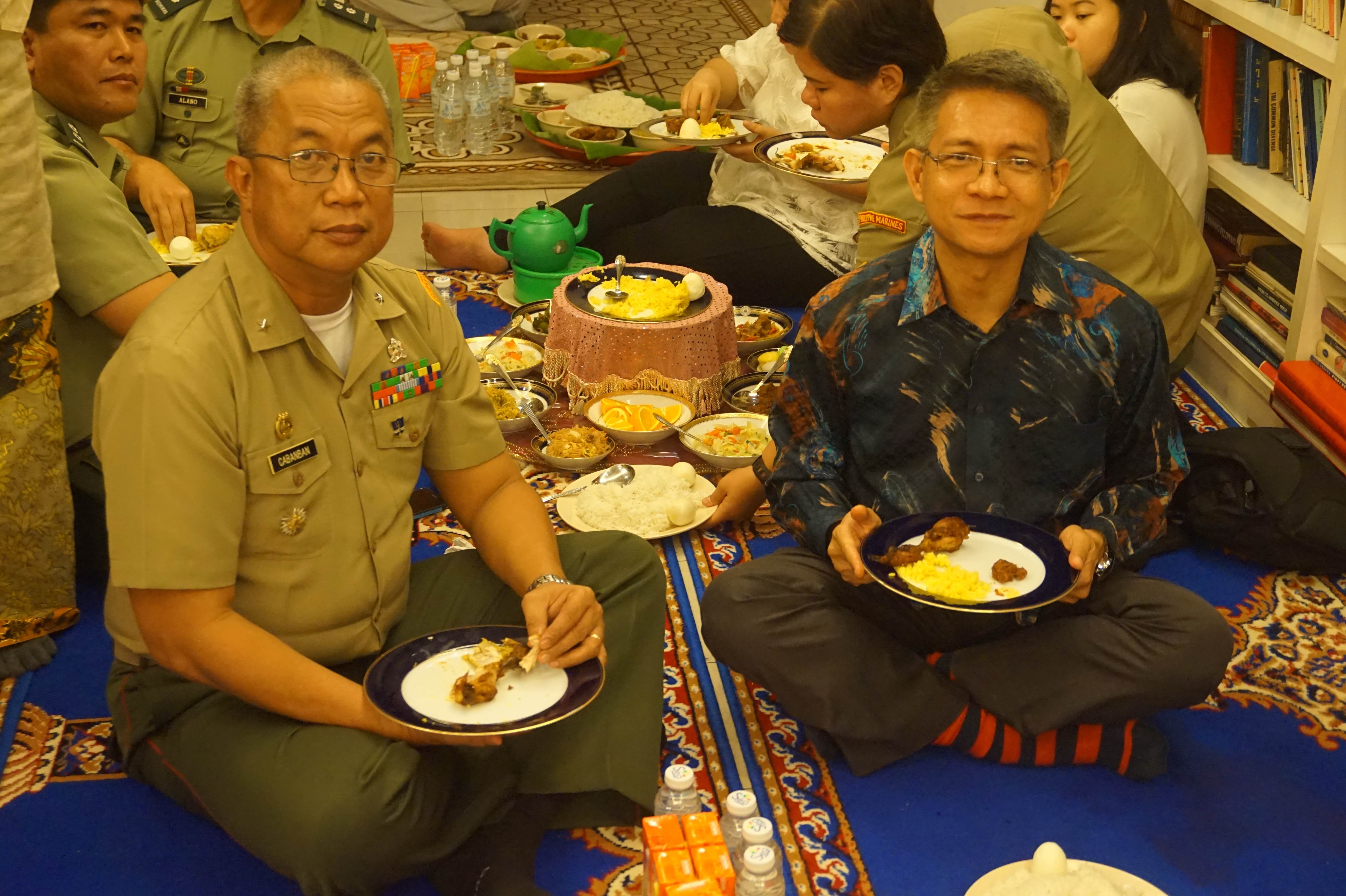 TRADITION. Cabanban and Ambassador Eduardo Malaya join the youth delegates on the carpeted floor for a traditional Muslim Filipino meal with the delegates. Photo by Carol Ramoran