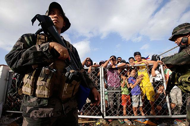WAITING. Typhoon victims queue for food at the gates of the Tacloban City airport. Photo by Dennis Sabangan/EPA