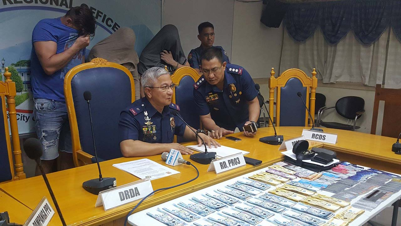 CONFISCATED. Central Luzon police director Chief Superintendent Aaron Aquino (seated) shows to media the seized cash and cloned ATM cards. Behind him are the 3 arrested foreigners. Also in photo is Pampanga police director Senior Superintendent Joel Consulta (right). Photo by Jun A. Malig/Rappler