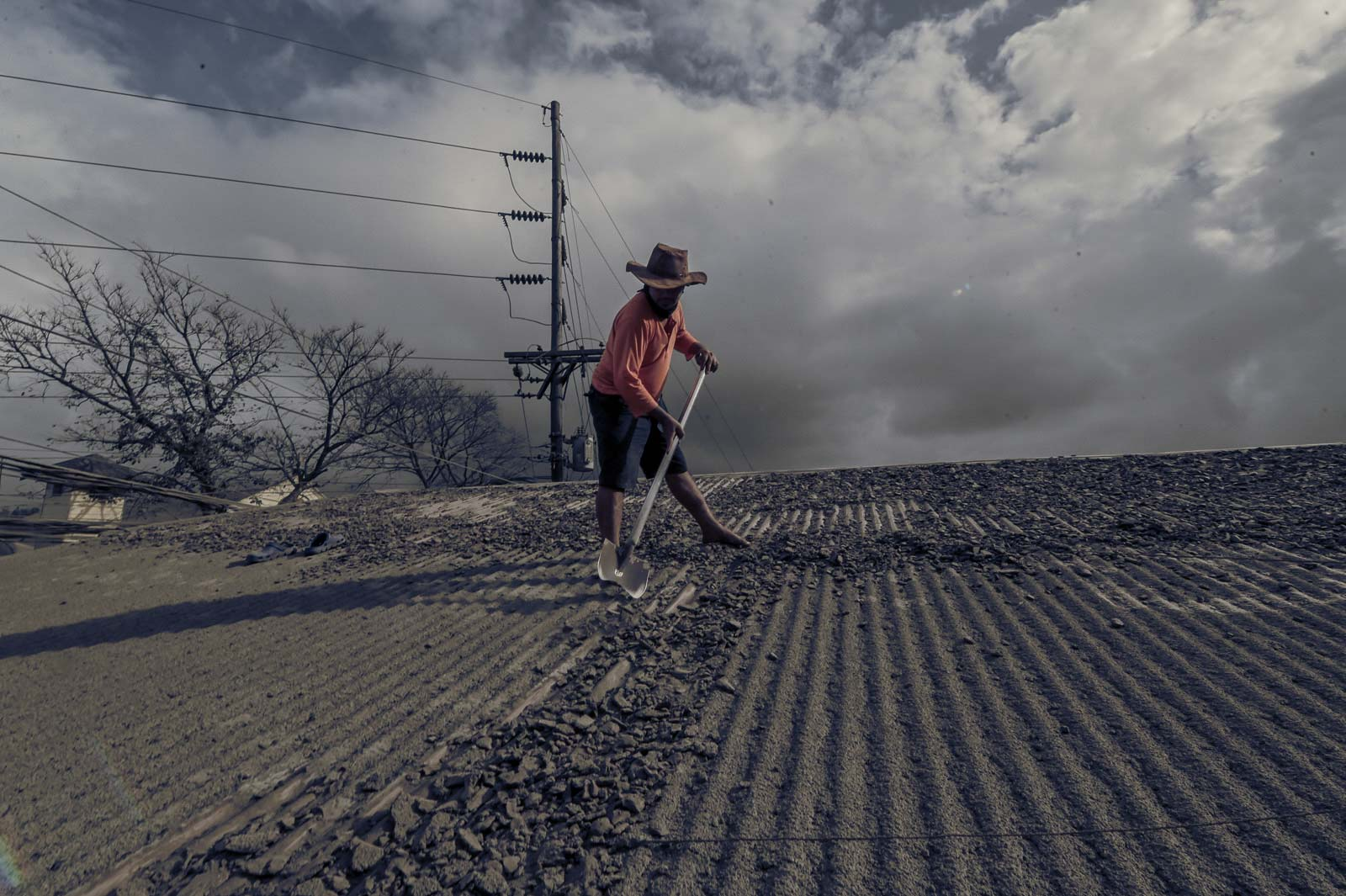 ASHFALL. A resident of Talisay, Batangas, scrapes ash off his roof on January 15, 2020. Photo by Alecs Ongcal/Rappler