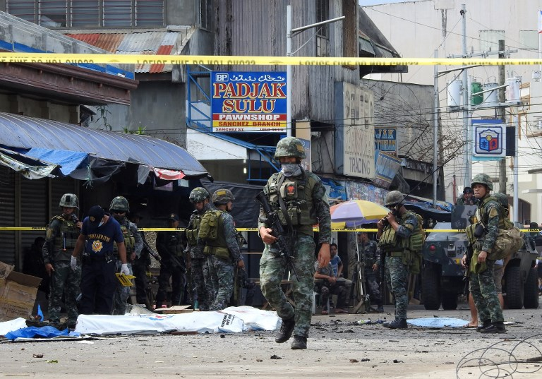 BLOODY SUNDAY. In this photo taken in Jolo on January 27, 2019, policemen and soldiers keep watch over body bags containing the remains of blast victims. Photo by Nickee Butlangan/AFP