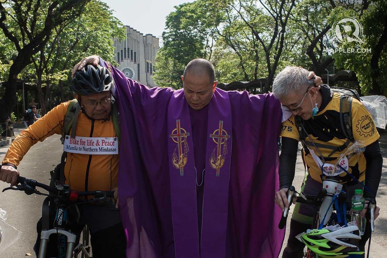 BLESSING FOR A SAFE JOURNEY. 'Running priest' Robert Reyes holds Father Picardal and lay person Chito Generoso before he sends them off to their 1500-kilometer bike trip.Photo by Eloisa Lopez / Rappler.com