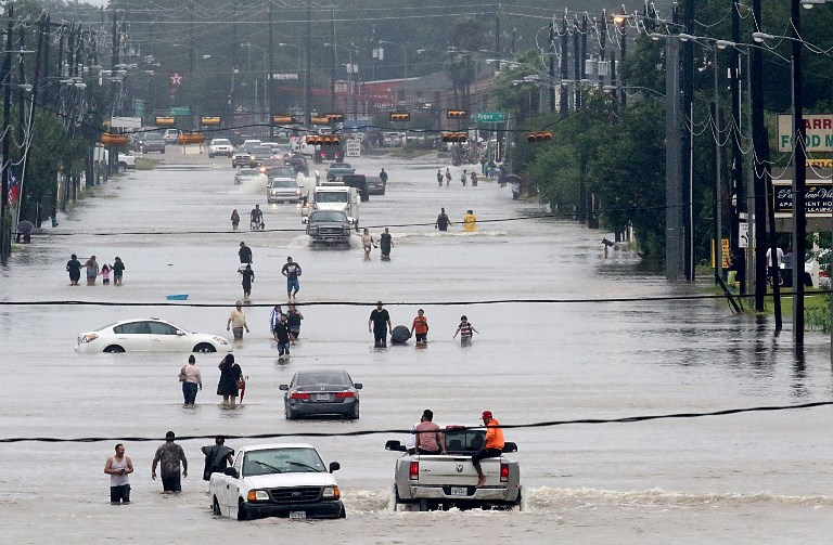 FLOODED. People walk through the flooded waters of Telephone Rd. in Houston on August 27, 2017 as the US's fourth city city battles with tropical storm Harvey and resulting floods. Thomas B. Shea/AFP