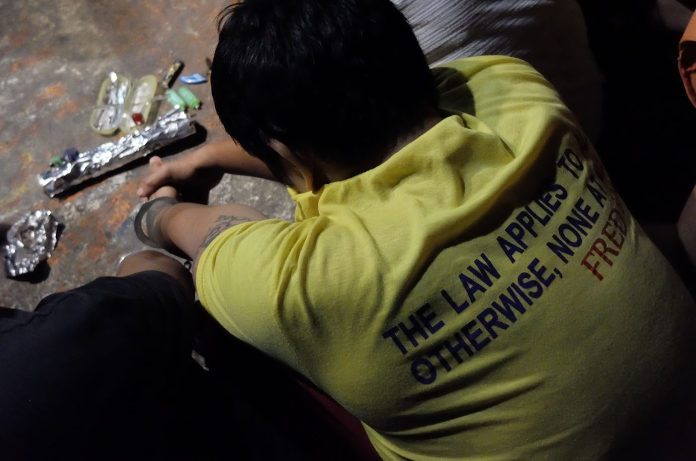 'DRUG PERSONALITY.' A drug suspect beside his alleged drug paraphernalia awaits processing by Manila police. Photo by Alecs Ongcal