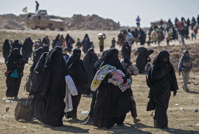 FINAL PUSH. Fully veiled women and children fleeing from the Baghouz area in the eastern Syrian province of Deir Ezzor walk in a field on February 12, 2019 during an operation by the US-backed Syrian Democratic Forces (SDF) to expel hundreds of Islamic State group (IS) jihadists from the region. Photo by Fadel Senna/AFP