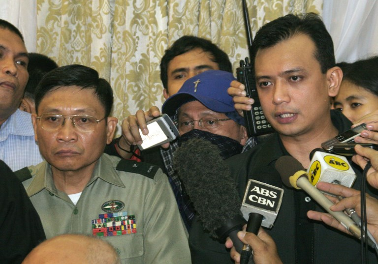 SIEGE ENDS. Philippine rebel officer, army Brigadier General Danilo Lim (L), looks on while Antonio Trillanes (R), a navy lieutenant who was elected senator in May, announces their surrender while government security forces assault the luxury Peninsula hotel room where they were holed up in Manila's Makati financial district, 29 November 2007. Photo by Jason Gutierrez/AFP