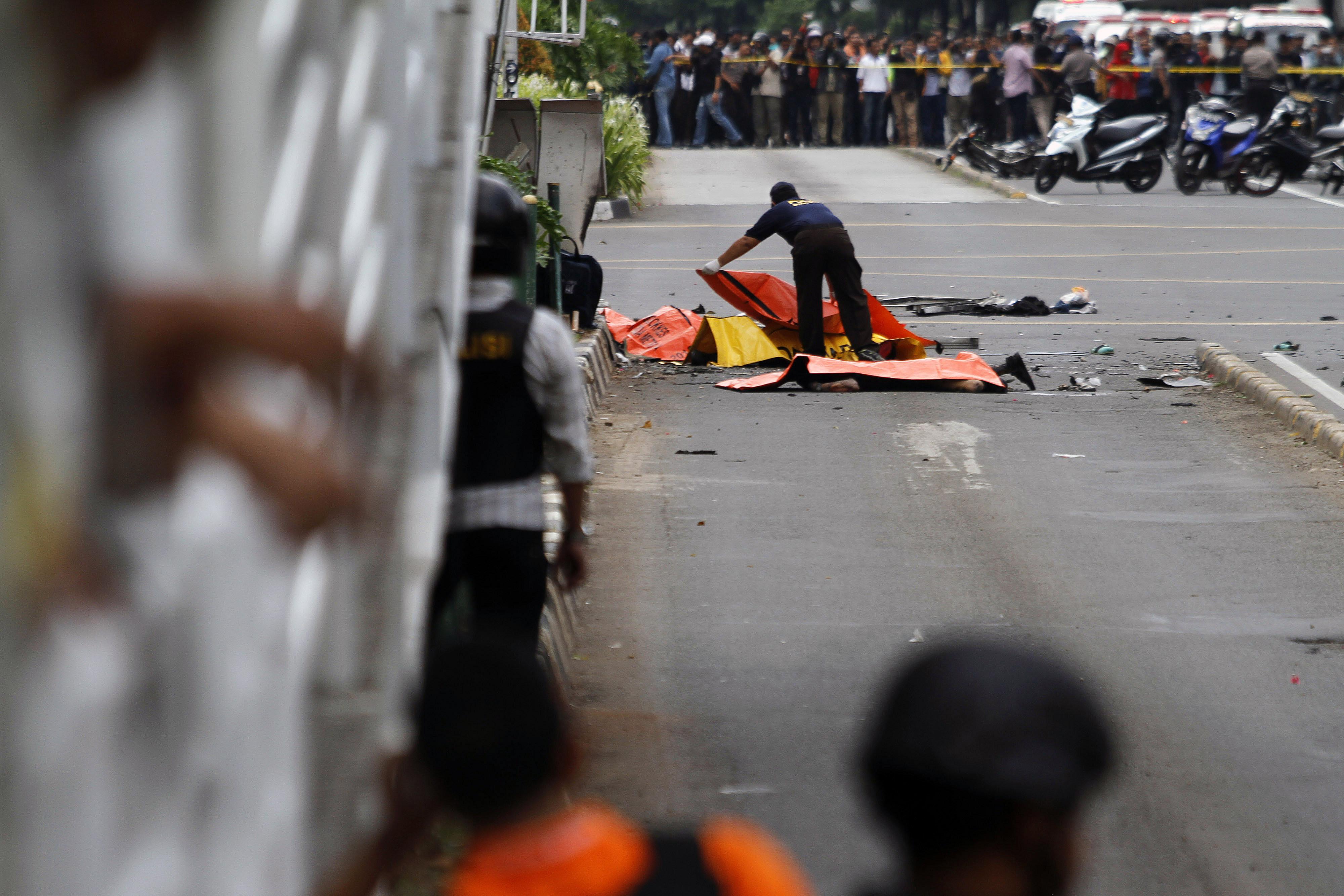 TEWAS. Polisi forensik sedang menutup jenazah korban yang tewas dalam serangan bom Sarinah, Jakarta, pada Kamis, 14 Januari lalu. Foto oleh Roni Bintang/EPA