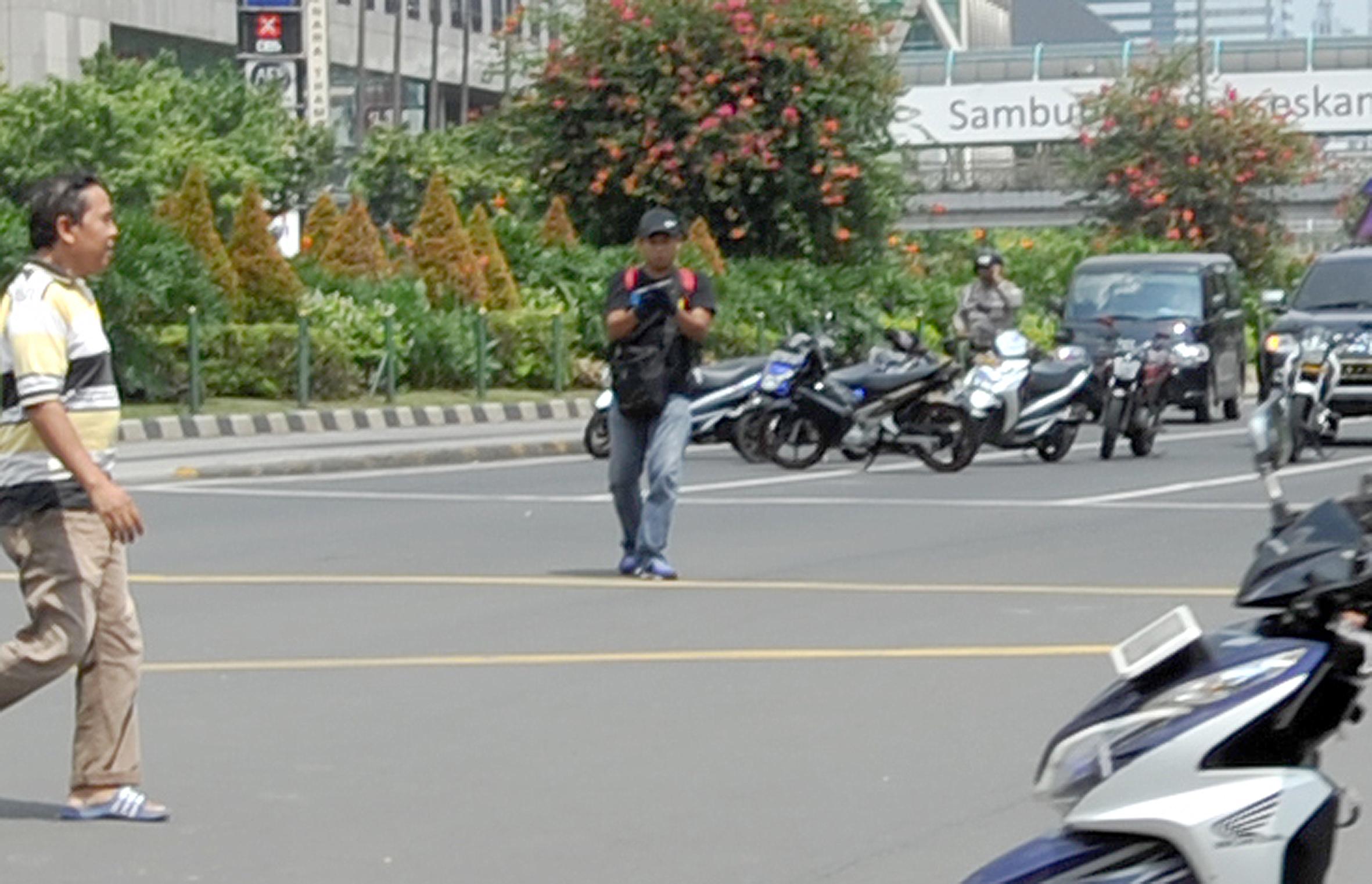 Seorang terduga pelaku peledakan dan penembakan teror Sarinah tertangkap kamera. Foto oleh Alfian/EPA