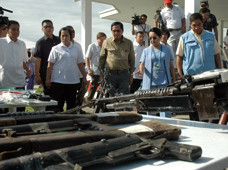 PEACE. Jesus Dureza (center) accompanies former president Gloria Arroyo (2nd R) as she inspects the firearms surrendered by communist rebels to the 4th Infantry Division of the Philippine Army on June 18, 2008. AFP photo