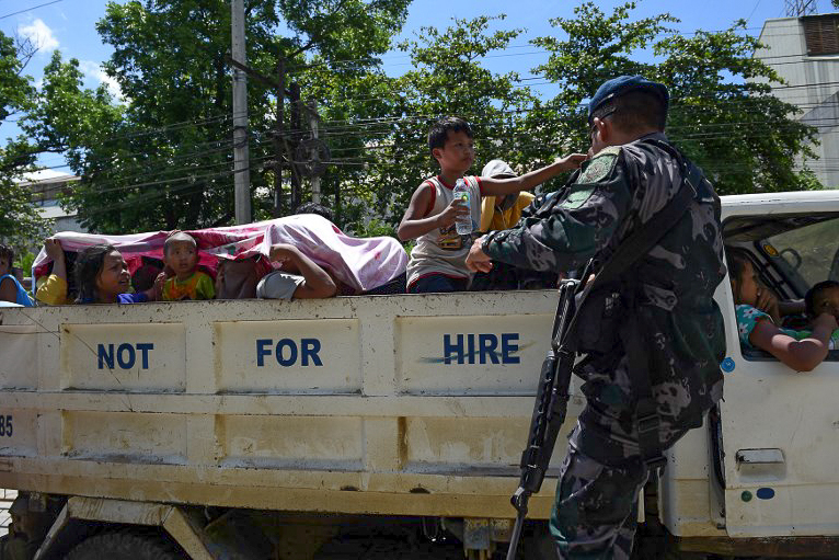 FLEEING MARAWI. A cop inspects a vehicle moving away from Marawi City on May 24, 2017. Photo by Ted Aljibe/AFP