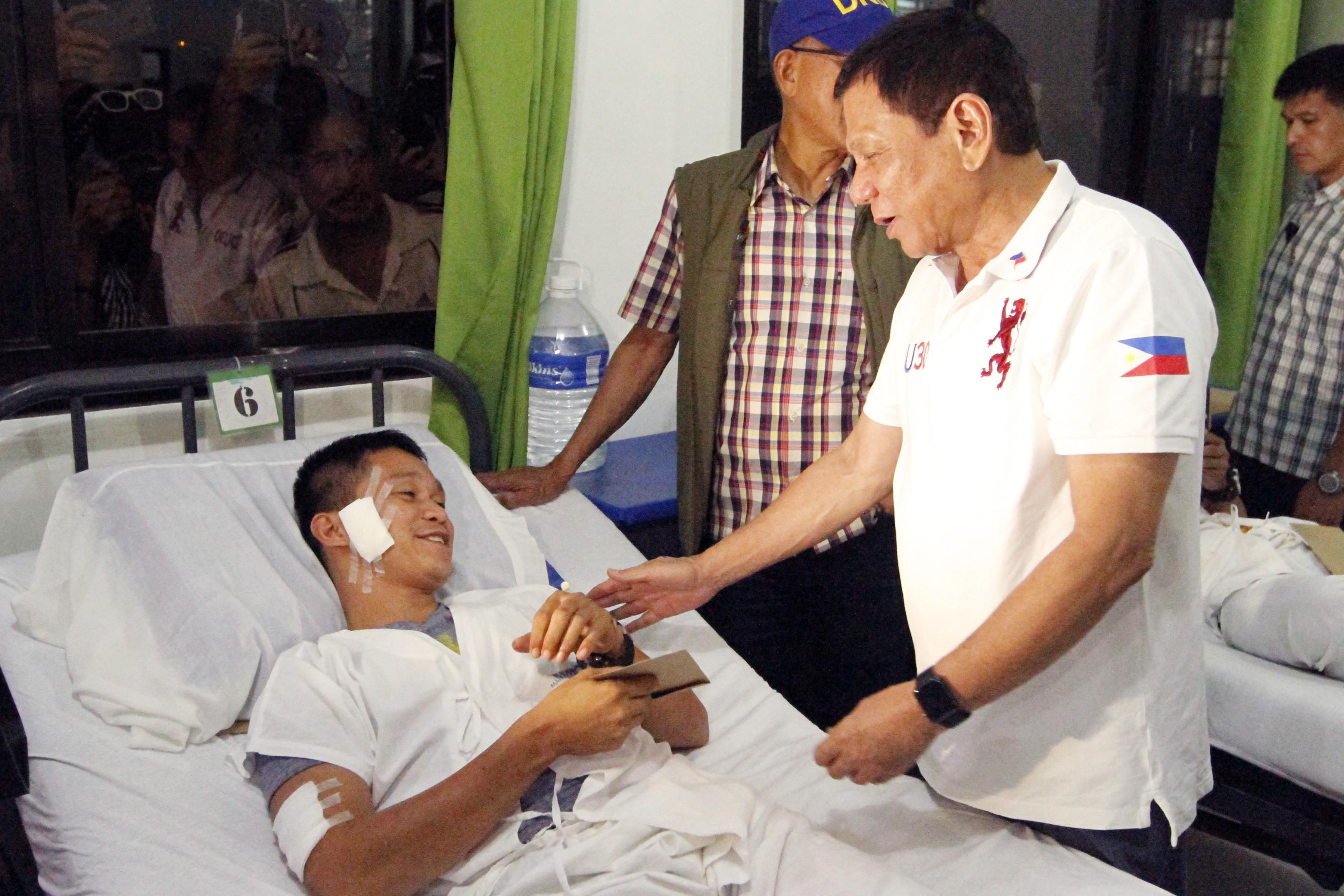 TRIBUTE TO THE WOUNDED. President Rodrigo Duterte visits a wounded soldier at Camp Navarro General Hospital in Zamboanga City on July 22, 2016. Photo by Benjamin Basug/NIB