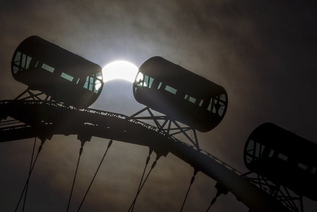 THE FLYER AND THE SUN. A partial solar eclipse is seen above cabins of the Singapore Flyer at dawn in Singapore, March 9, 2016. Wallace Woon/EPA