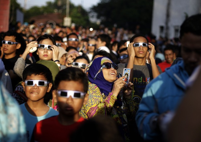 EAGER CROWD. Indonesian residents wearing eclipse glasses look up at the sun during a solar eclipse outside the planetarium in Jakarta, Indonesia, March 9, 2016. Mast Irham/EPA