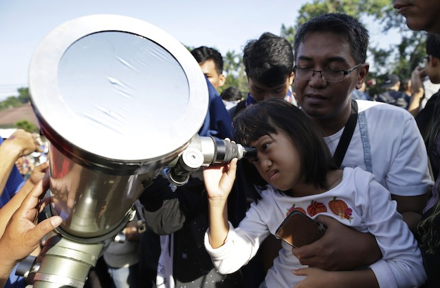 THROUGH THE TELESCOPE. An Indonesian young girl looks up at the sun through a telescope during a solar eclipse outside the planetarium in Jakarta, Indonesia, March 9, 2016. Mast Irham/EPA
