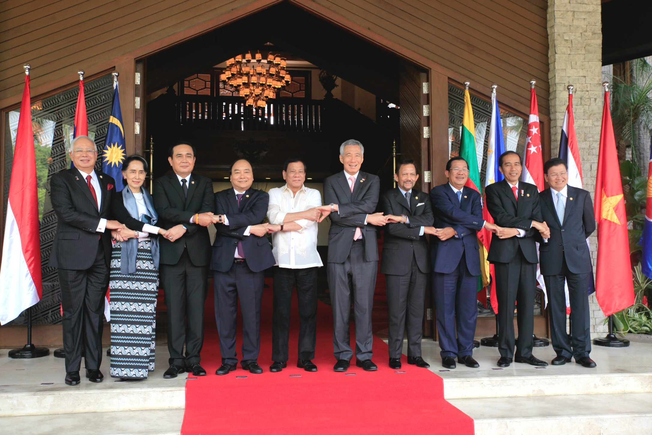 Malaysian Prime Minister Najib Razak (1st L), Myanmar State Counsellor Aung San Suu Kyi (2nd L), Thailand Prime Minister Prayuth Chan-o-cha (3rd L), Vietnamese Prime Minister Nguyen Xuan Phuc (4th L), Philippine President Rodrigo Duterte (5th L), Singapore Prime Minister Lee Hsien Loong (5th R), Sultan of Brunei Hassanal Bolkiah (4th R), Cambodian Prime Minister Hun Sen (3rd R), Indonesian President Joko Widodo (2nd R), Laos Prime Minister Thongloun Sisoulith (1st R) hold hands during the group photo of the 30th Association of Southeast Asian Nations (ASEAN) Summit at the Coconut Palace in Pasay City on Saturday, April 29, 2017. Pool Photo