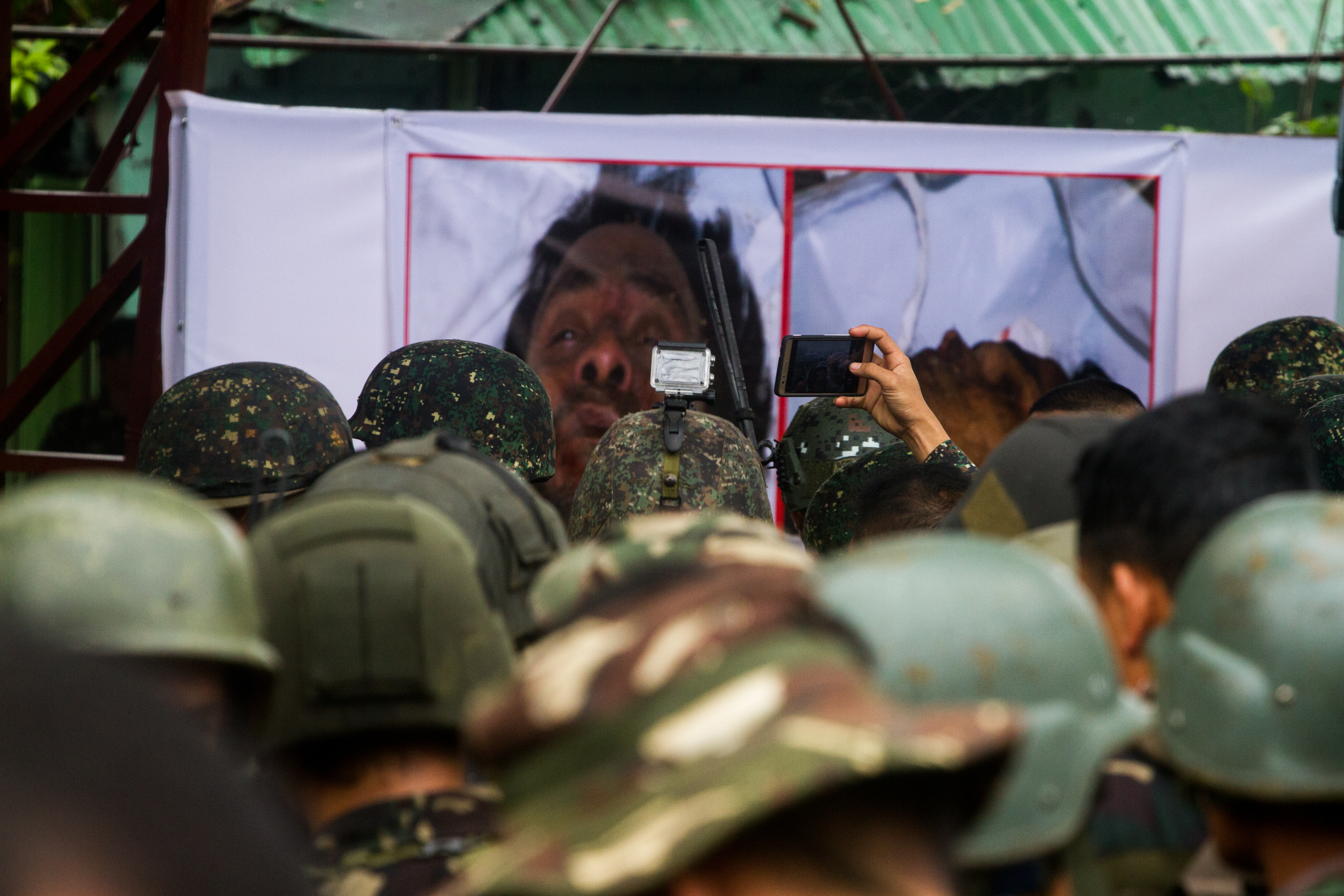 KILLED. Troops stare at enlarged photos of the dead bodies of terror leadres Isnilon Hapilon and Omar Maute