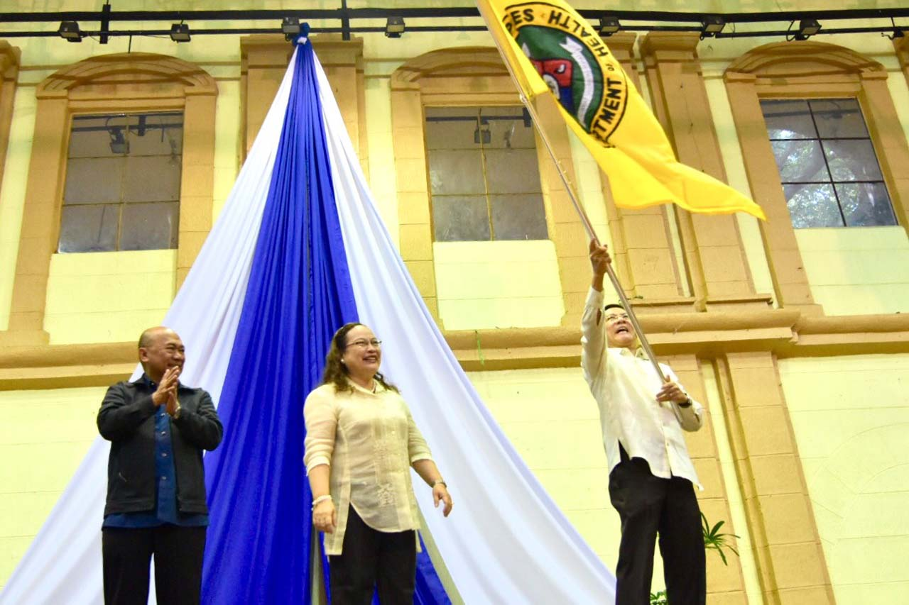 NEW CHIEF. Ubial looks on as Duque waves the DOH flag, signifying the change in leadership. Photo by LeAnne Jazul/Rappler