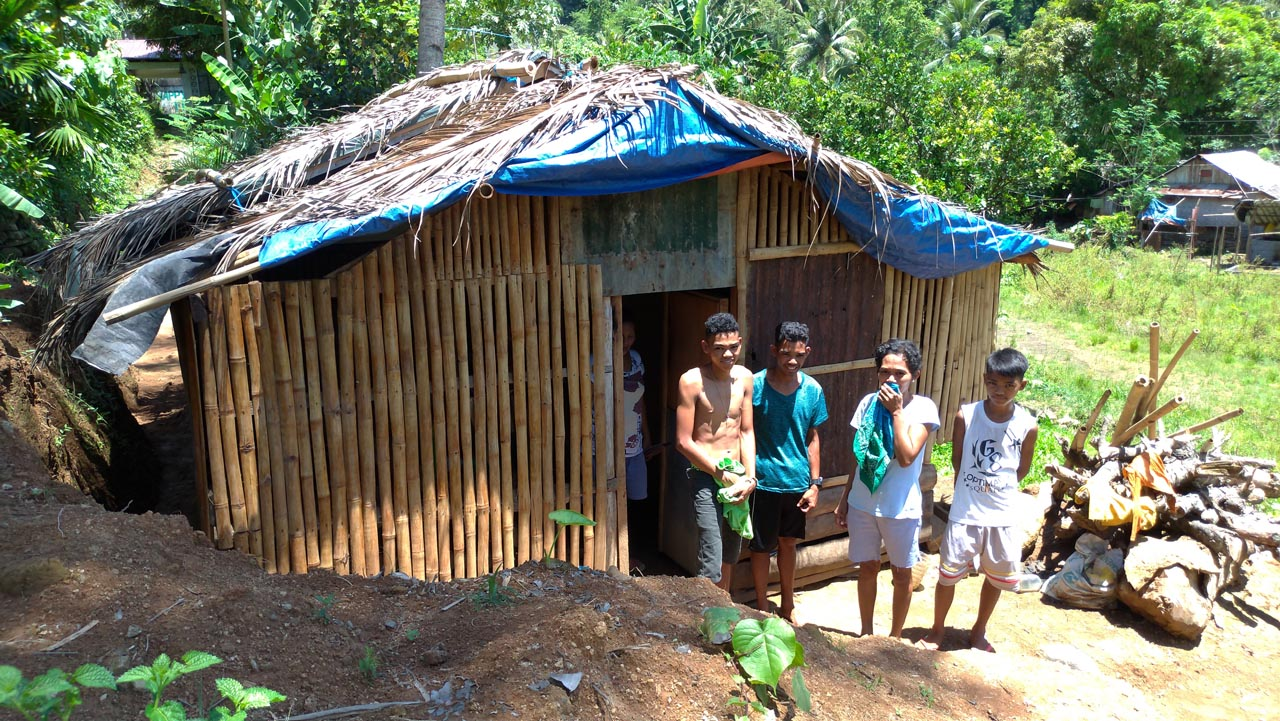 SOLO PARENT. Elsa Bau00f1ares and her three sons in front of their newly built home.u00a0Photo by Mavic Conde/Rappler