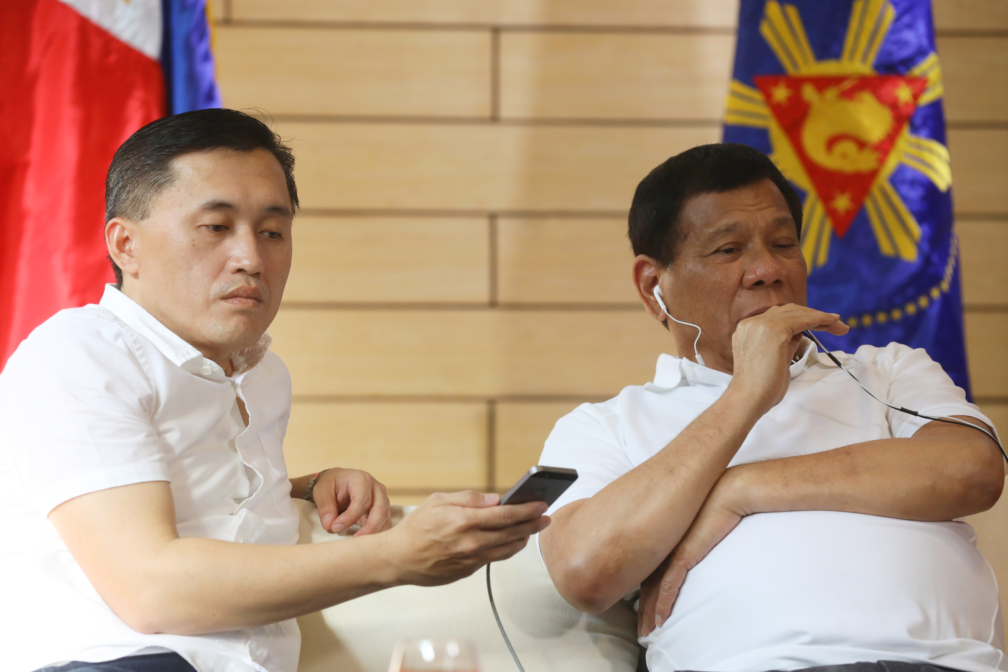 GATEWAY TO DUTERTE. Special Assistant to the President Bong Go helps President Duterte during his phone call with Chinese leader Xi Jinping. Presidential photo