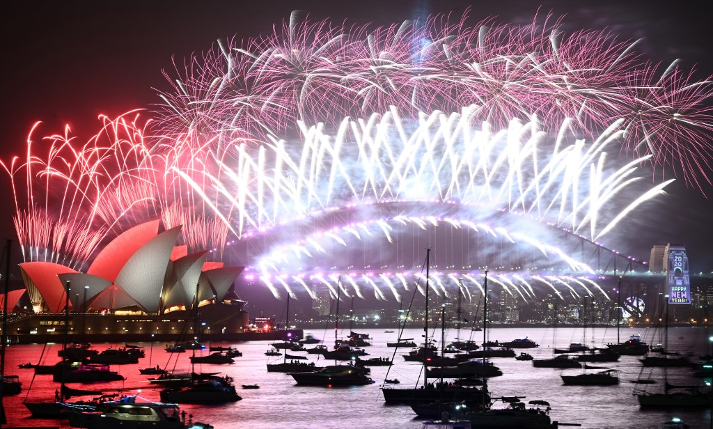 SYDNEY. New Year's Eve fireworks erupt over Sydney's iconic Harbour Bridge and Opera House (L) during the fireworks show on January 1, 2020. Photo by Peter Parks/AFP