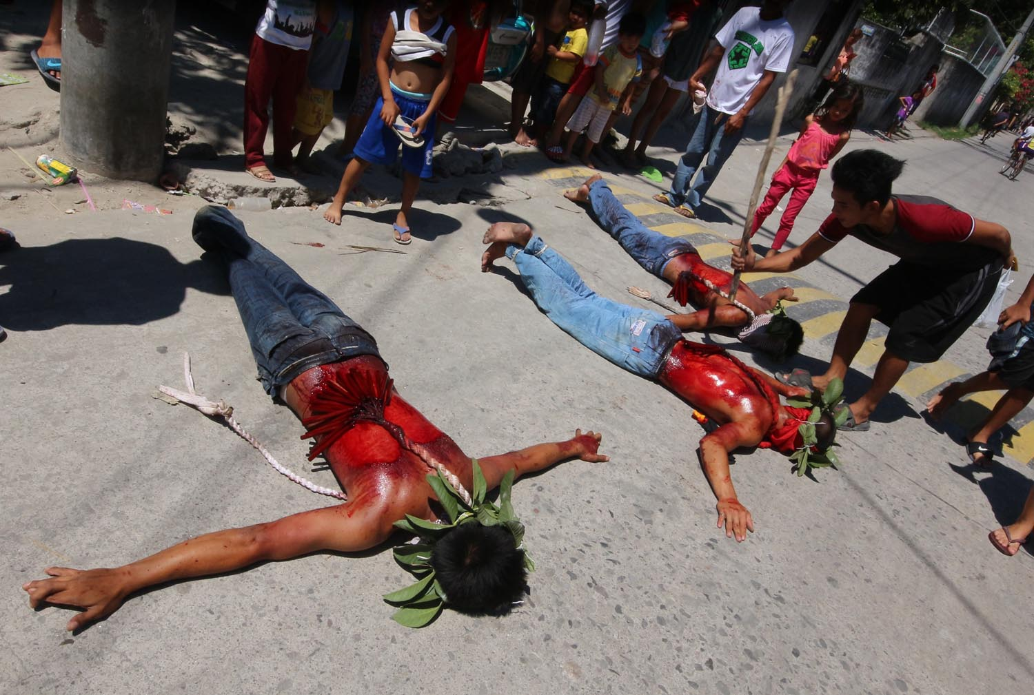 OFFERING. A man whips a devotee lying on the ground. Photo by Darren Langit