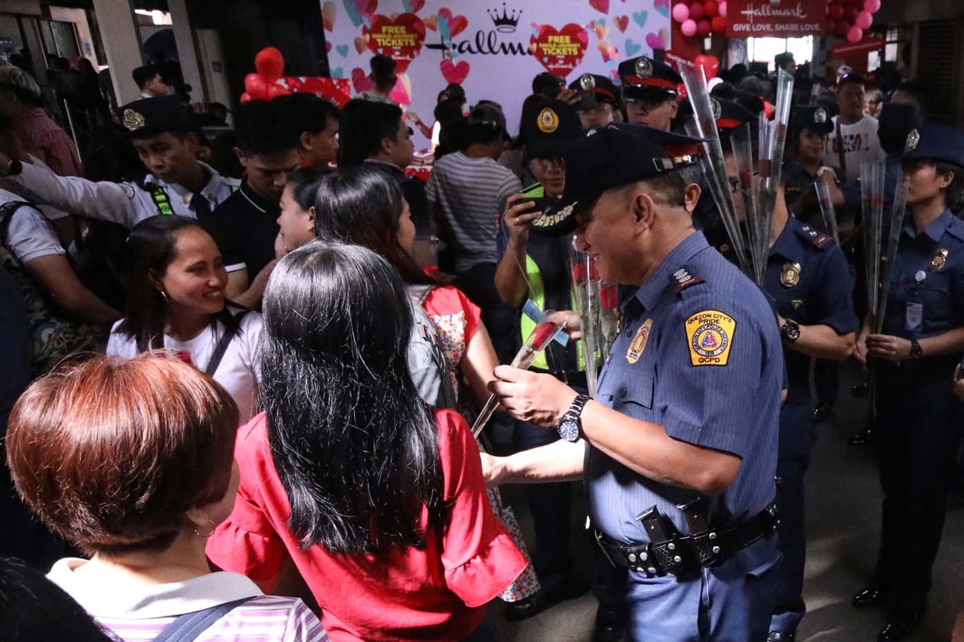 ROSES FOR ALL. Cops from the Quezon City Police District give away roses to commuters in Cubao. Photo by Darren Langit/Rappler