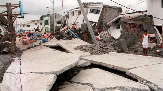 CHERRY HILLS. A man looks at a cracked road running past collapsed houses in the Cherry Hills residential subdivision of suburban Antipolo on August 4, 1999, following a landslide. File photo by Romeo Gacad/AFP