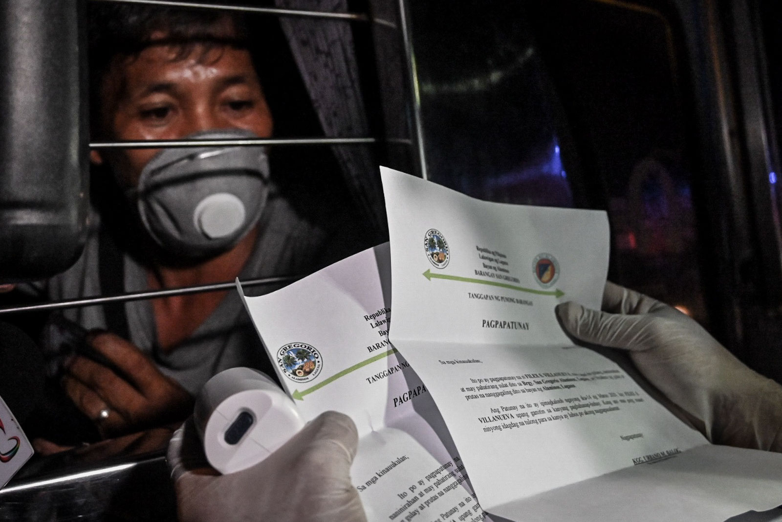 A DOH personnel checks body temperatures of motorists as policemen inspect their identification at a checkpoint along the boundary of Muntinlupa and San Pedro, Laguna. Photo by Alecs Ongcal/Rappler
