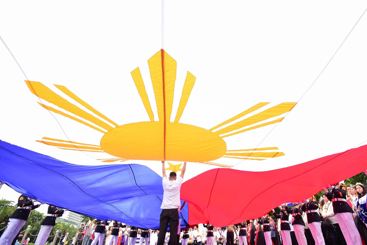 THE FLAG. A man helps hold up a big Philippine flag used during the Independence Day rites in Luneta Park. Photo by Maria Tan/Rappler