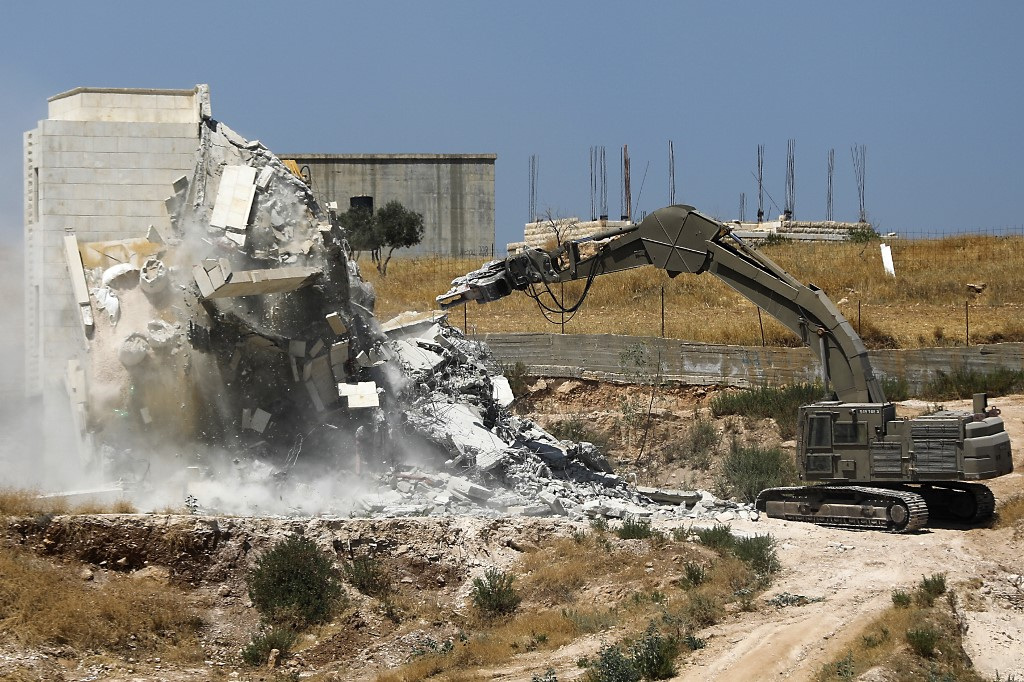 DEMOLITION. This picture taken from Jerusalem on July 22, 2019, shows Israeli security forces tearing down one of the Palestinian buildings still under construction which have been issued notices to be demolished in the West Bank village of Dar Salah, adjacent to the Sur Baher area which straddles the West Bank and Jerusalem. Photo by Ahmad Gharabli/AFP
