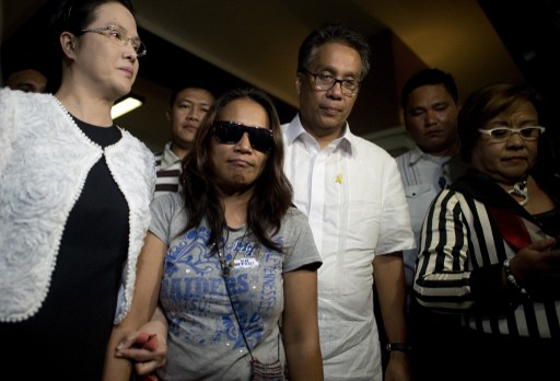ILLEGAL RECRUITMENT CASE. In this photo taken on April 29, 2015, alleged recruiter Maria Cristina Sergio is escorted by Public Attorneys Office (PAO) chief Persida Acota and former Interior secretary Mar Roxas after Sergio turned herself in to authorities. Photo by Noel Celis/AFP
