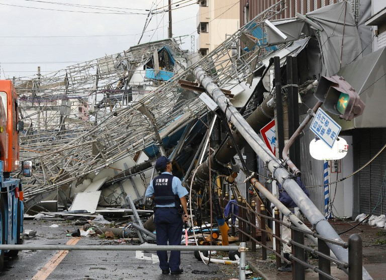 Damaged traffic boards and telecommunication relay poles are seen after they were brought down by strong winds caused by Typhoon Jebi in Osaka on September 4, 2018. Photo by Jiji Press/AFP