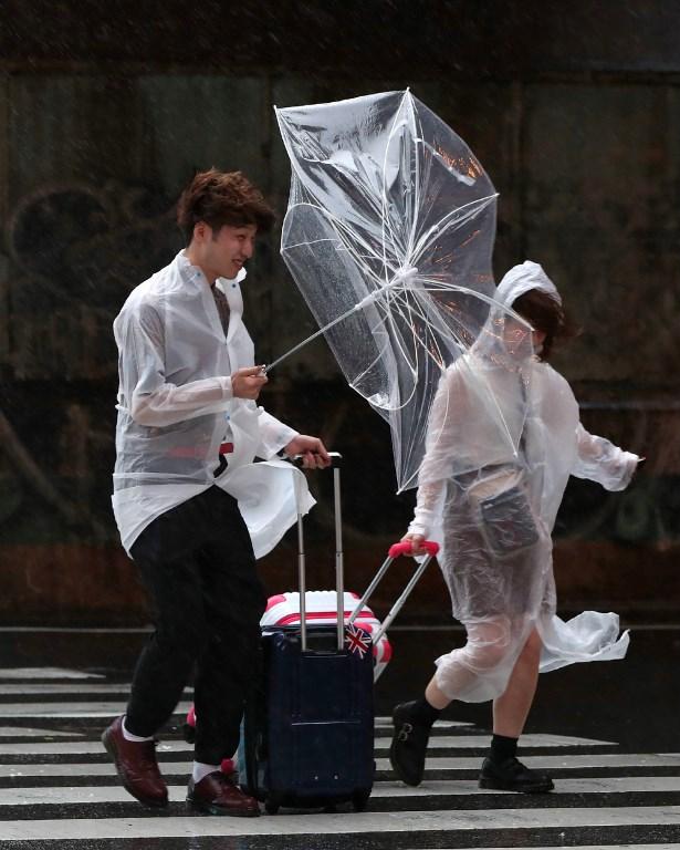 A couple walks in heavy wind and rain near Osaka station on September 4, 2018, as Typhoon Jebi made landfall around midday in southwestern Japan. Photo by Jiji Press/AFP