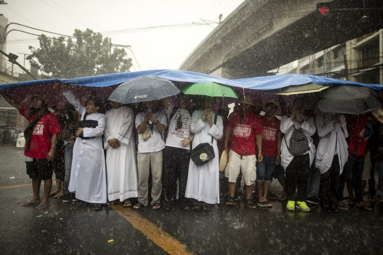 DESPITE RAIN. Protesters take shelter from the rain during a protest to commemorate the 46th anniversary of the declaration of Martial Law by the late dictator Ferdinand Marcos in Manila on September 21, 2018. Photo by Noel Celis/AFP